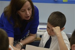 Third grade teacher Colleen Koch talks with Domenic Catandro about his paper. Students at St. Sebastian School are writing cards and letters to World War II veterans who will be honored with flights to Washington next month.