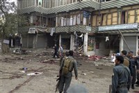 Afghan security forces inspect the site of a suicide attack near a bank branch in Jalalabad, east of Kabul, Afghanistan.