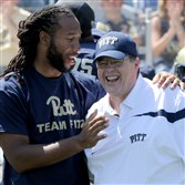Former Pitt star and Arizona Cardinals wide receiver Larry Fitzgerald talks to Pitt offensive coordinator Jim Chaney during the Blue-Gold Game in April at Highmark Stadium.