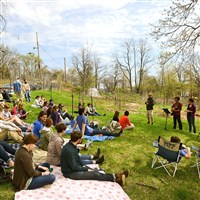 Members of the Open Door Church at Garfield Community Farm gather under budding trees to worship in the open air. The open-air service mixed traditional worship and singing with chores at the urban farm. Among them were baking the communion bread in a wood-fired oven.