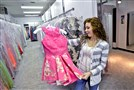 Marissa Miller, the daughter of the owners of My Sissy's Closet in Greensburg, checks a prom dress in the shop April 20. This is a Sherri Hill two-piece pink print. All of the dresses sold in the shop are new. The store does not do consignment.
