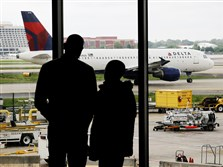 Travelers watch as a plane taxis on April 14 at Hartsfield-Jackson Atlanta International Airport in Atlanta. After years of steadily rising airfare, travelers this summer can expect a tiny bit of relief.