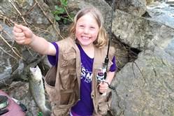 With a little help from grandfather Greg Stephans of Monroeville, Riley Stephans, 7, of Plum was thrilled to catch this brown trout at Turtle Creek in Level Green.