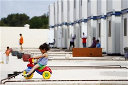 A child migrant plays on a tricycle outside prefabricated container houses at the Hal Far Tent Village open centre outside Valletta in September 2014.