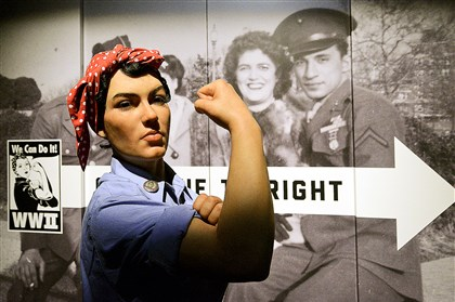 "A life-size replica of the famous woman assembly line worker from the ""We Can Do It!"" poster greet visitors at the Heinz History Center's exhibit on Pittsburgh during World War II."