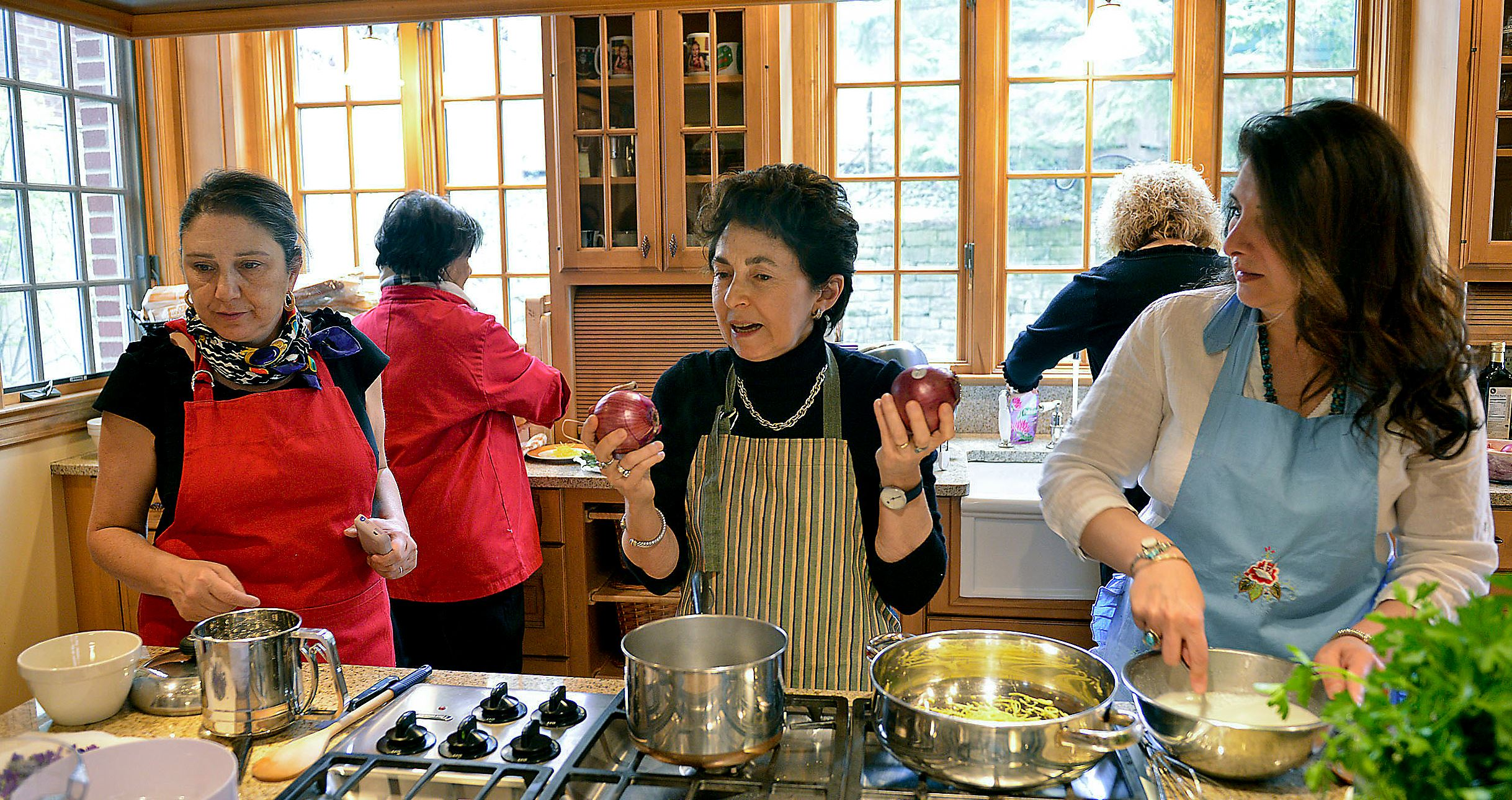 20150423lritalianseen08-4  The Duchess Nicoletta Polo Lanza Tomasi, center, a cooking teacher, talks about using red onions to inject color into a rustic country potato salad as Miki Fato, left, and Patrizia Cost-Frezza, right, listen.