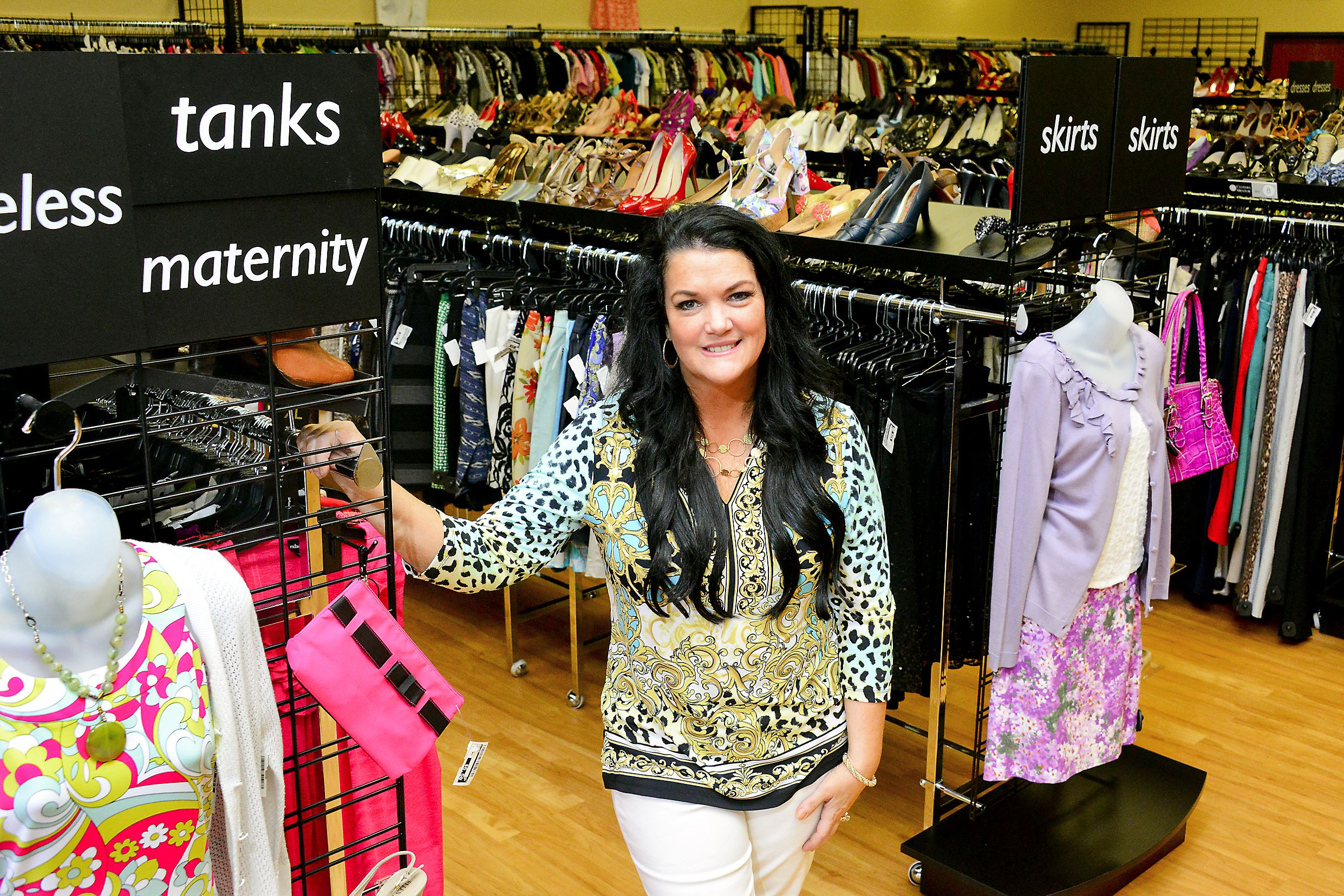 Superior Clothes Mentor Franchisee Andrea Zabinski Standing In Her Organized Store  Full Of Clothes Racks With Shelves