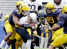 West Virginia linebacker Xavier Preston (53) tackles West Virginia running back Donte Thomas-Williams (8) in the Gold-Blue spring game Saturday in Morgantown, W.Va.  (AP Photo/Raymond Thompson)