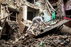 A man climbs on top of collapsed buildings Sunday in Bhaktapur, Nepal, a day after parts of the nation were devastated by a 7.8 -magnitude earthquake.
