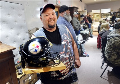 James Freeman of Ohio displays the replica Steelers helmet-telephone that he purchased Sunday at the auction of former Steeler L.C. Greenwood's estate at Johnson Auction Services in Moon.