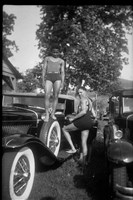 "Charles ""Teenie"" Harris; William Harris III in bathing suit, standing on spare tire on running board of Duesenberg, with man opening door, c. 1934-1936."