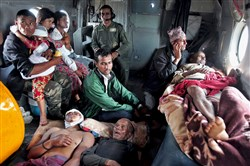 Victims of Saturday's earthquake rest Monday inside an Indian Air Force helicopter as they are evacuated from Trishuli Bazar to the airport in Kathmandu, Nepal.