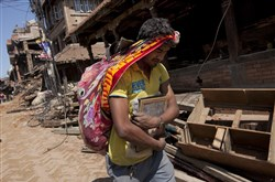 A Nepalese man carries his belongings from earthquake debris in Bhaktapur, on the outskirts of Kathmandu, Nepal, today. A strong magnitude earthquake shook Nepal's capital and the densely populated Kathmandu valley on Saturday devastating the region and leaving tens of thousands shell-shocked and sleeping in streets.