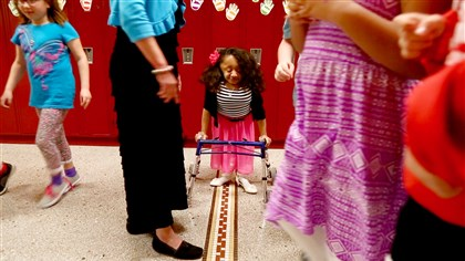 Lexie Bouchard, a seventh-grader at Pittsburgh Brookline PreK-8 who has a rare bone disease, stands in the hallway Thursday after posing for a group photo.