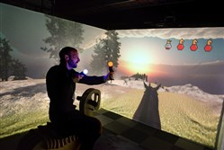 Stone Librande of Riot Games and the Carnegie Mellon University's Entertainment Technology Center plays through a trial of CAVE Men, which utilizes a three-walled projection. The ETC hosted a showcase of its current students' projects Thursday at its Technology Drive location.