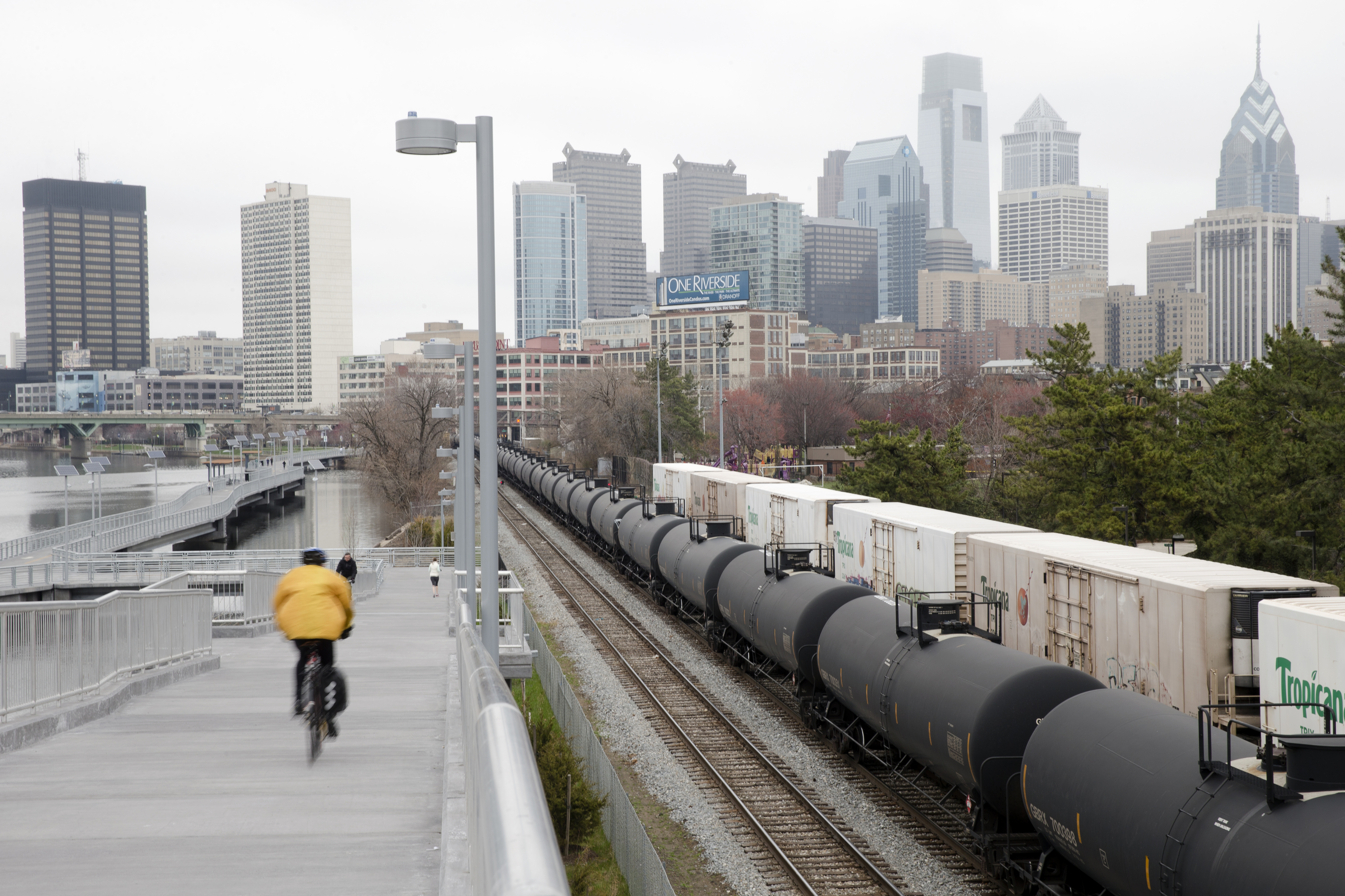 Oil Train Rules-4 In this photo taken April 9, 2015, a cyclist rides by train tank cars with placards indicating petroleum crude oil standing idle on the tracks, in Philadelphia. Rail tank cars that are used to transport most crude oil and many other flammable liquids will have to be built to stronger standards to reduce the risk of catastrophic train crash and fire under a series of new rules unveiled Friday by U.S. and Canadian transportation officials.