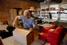 Jay Fanelli, 35, of Collier, one of the founders of Cotton Bureau, helps to pack a shipment of T-shirts from the company's Strip District location.