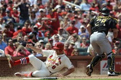 The Cardinals' Peter Bourjos scores as the Pirates' Francisco Cervilli can't reach the throw in the sixth inning.