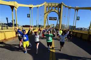 Runners jog across the Roberto Clemente Bridge toward Downtown during the Pittsburgh 5K Run.