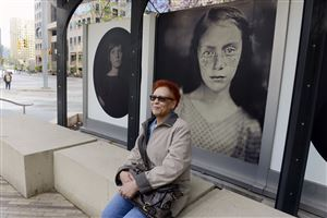 Arberna Holloway of East Liberty sits in Triangle Park in front of the Fairmont Pittsburgh, Downtown, with photographs from the Magenta Foundation outdoor display.