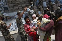 Nepalese army distribute drinking water and packed noodles Sunday for people who have had their homes damaged and living in tents after the April 25 earthquake in Kathmandu, Nepal. With monsoon rains expected in a few weeks, Nepal has pleaded with donors to send tents and temporary shelters for earthquake victims who have been living in the open for more than a week.
