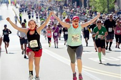 Kelsey Ewing (left) of Middleport, Ohio, and Chelsea Freeman of Athens, Ohio, whooped it up together as the approached the finish line at the 2015 Pittsburgh Marathon.