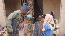 In this photo made available by the Nigerian military taken last Wednesday, a Nigerian soldier speaks to a woman and children that were allegedly rescued by the Nigerian military after being taken by Islamic extremists in Sambisa Forest, Nigeria.
