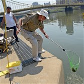 Morgan Hezlep of Pleasant Hills lands a 12-inch small mouth bass on the first day of Venture Outdoors TriAnglers fishing program on the North Shore outside PNC Park last month. At left is Maurice Moore of Pittsburgh's Oak Hill neighborhood.