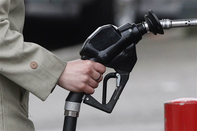 A filling station attendant pumps gas in Portland, Ore.