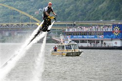 "Riding on jets of water, ""Tommy Typhoon"" Nuttel gives the passengers on the Gateway Clipper Empress a show as he races his Jetorator over the Ohio River today during the news conference announcing this year's EQT Three Rivers Regatta lineup of events."