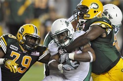 Shawn Lemon, left, and Ted Laurent, right, of the Edmonton Eskimos tackle Saskatchewan Roughriders' Kory Sheets during an August 2012 CFL game.
