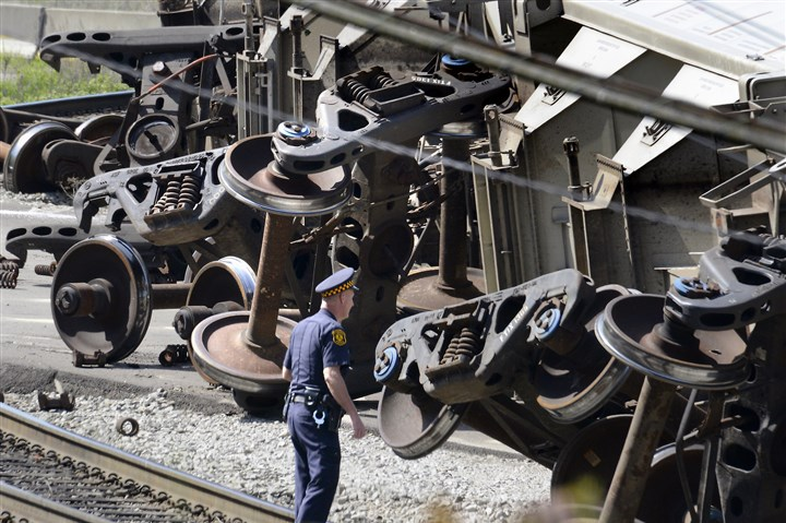 20150514dsDeRailmentLocal01 A police officer stands on the railroad tracks in Hazelwood where a freight train derailed this morning near Irvine Street.