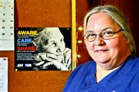 "Terri Ploskina displays an ""I Care"" poster on a bulletin board in her establishment, Dot's Family Restuarant in McKeesport."