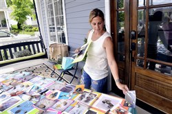 "Julie Farber, who teaches jewelry and metalshop at Taylor Allderdice High School in Squirrel Hill, arranges photos of the jewelry that she and her students created for their group "" Jewelry Love,"" which  provides jewelry to women cancer survivors and those undergoing chemotherapy, during the Summerset Porch Party on Sunday"