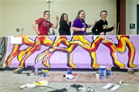 Josh Francis, Olivia Airhart, Emma Skreppen and Nicole Kurka, all 12th-graders, have a little fun with a Jersey barrier they painted.