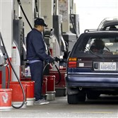In this May 6, photo, cars line up as an attendant pumps gas at a station in Portland, Ore.