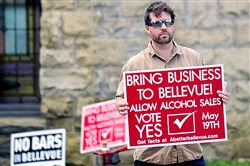 Aaron Stubna holds up a sign in support of legalizing alcohol sales in Bellevue Tuesday. Unofficial results indicate residents in Bellevue and Wilkinsburg voted on ballot questions to legalize liquor sales in their communities.