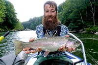 Wilderness Voyageurs fishing guide Ryan McCauley holds a nice Youghiogheny rainbow.