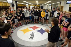 Heinz Field tour guide Linda Rashiatore leads a group of students from schools which received the Steelers's Touchdown Award in the NFL Play 60 initiative on a tour of Heinz Field in the team's locker room before an award luncheon.