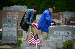 "World War II veteran Clarence ""Code"" Gomberg of Stanton Heights and Josh Berger, 12, a sixth grader from Community Day School in Squirrel Hill, replace the weathered American flags with new flags at Adath Jeshurun Cemetery in Hampton on May 20."
