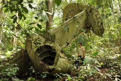 Chief Petty Officer Jared Krueger stands near the wreckage of Charles Johnston's B-24 in Papua New Guinea on Aug. 18, 2010. A government recovery team first found the plane in 2001, and returned four times over the course of the decade to excavate the area for remains and evidence useful in the identification process.