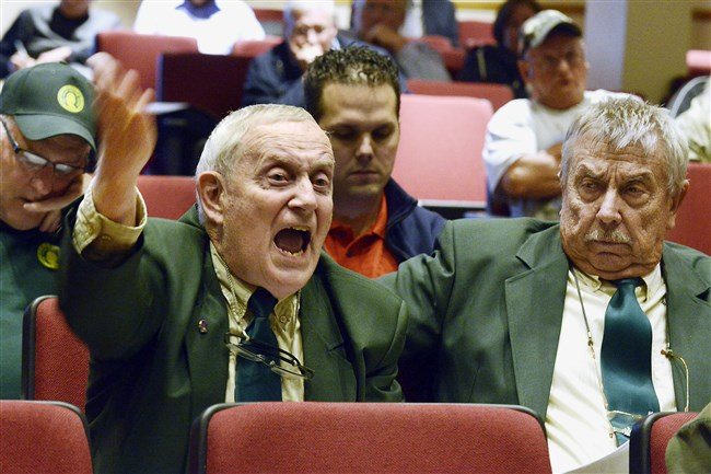 Charles Hunnell of Waynesburg, left, a member of the Izaak Walton League of America, an environmental group, with fellow member Ken Dufalla, right, of Clarksville, asks questions Thursday of representatives of the state Department of Environmental Protection and FirstEnergy at Carmichaels High School. The company wants to transfer waste from its