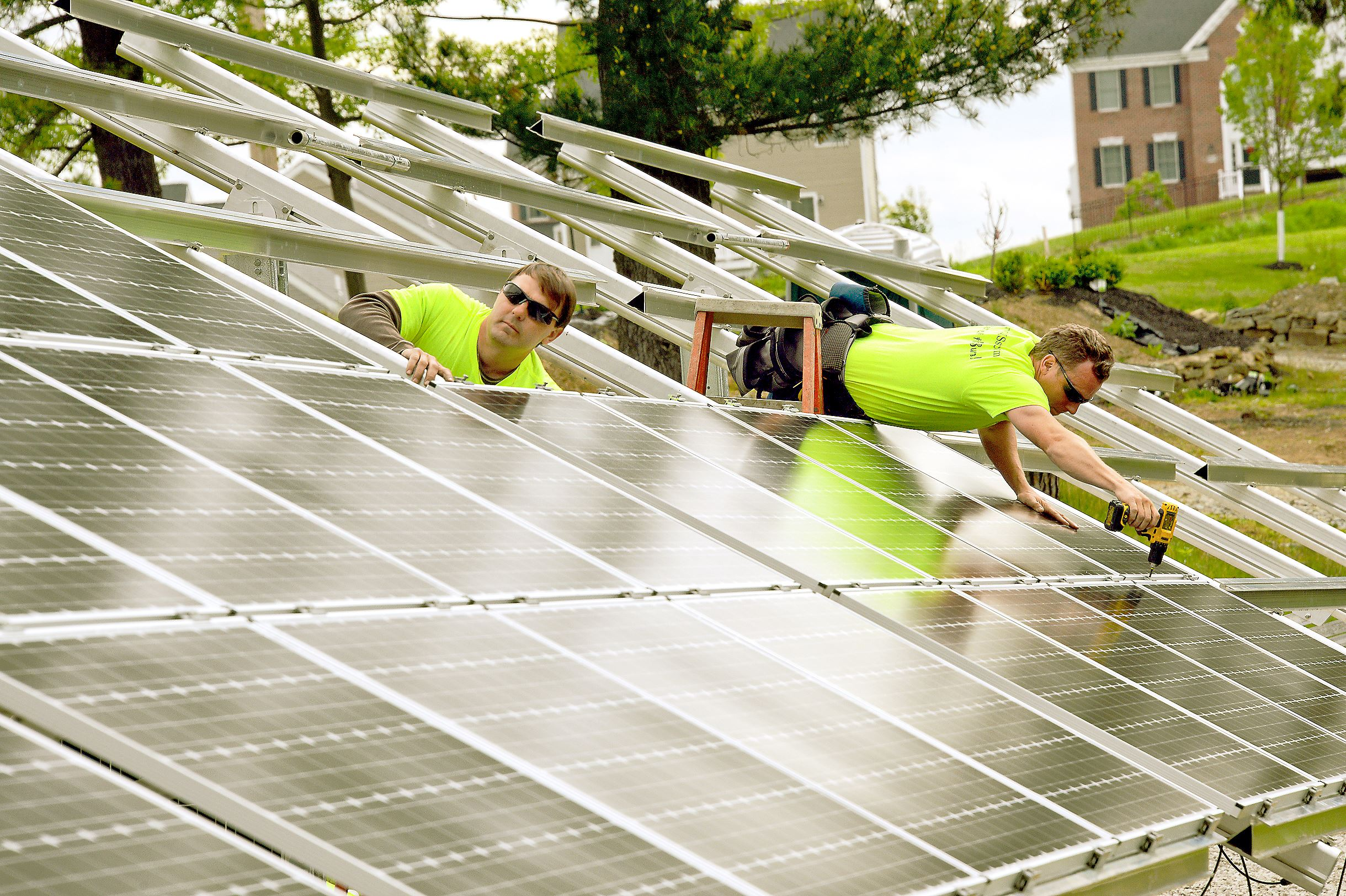 20150521lfSolar02-1 Brian Krenzelak, left, and Scott Rhodehamel of Energy Independent Solutions install solar panels in Moon on May 21. The installation spanned 125 feet in length and can generate more than 30,000 kilowatt-hours each year.