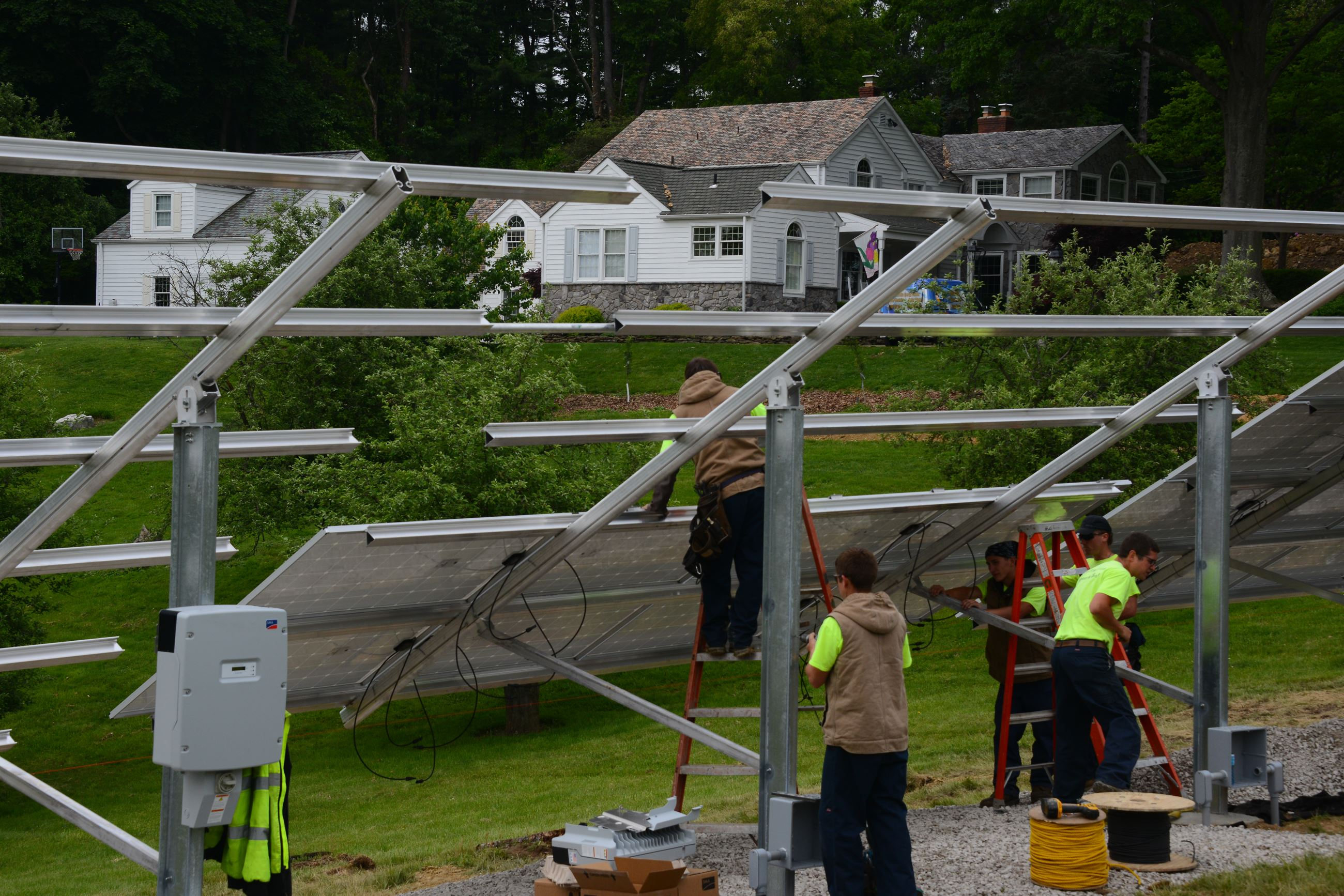 20150521lfSolar01 Workers from Energy Independent Solutions install solar panels on the front yard of the house in Moon on May 21. The installation spanned 125 feet in length and can generate more than 30,000 kilowatt-hours each year.