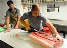 Mike LaMantia, executive chef of Market St. Grocery, butchers a pig while James Phelps helps at the Downtown store.