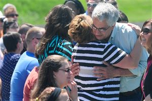 Bill Rosetti, South Park High School's chorus director, is greeted by former students and their families at a surprise retirement party organized for him at the school's football field on Saturday.