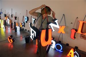 "MaryEllen Lammel of Upper St. Clair spells out FUN with recycled store signs at the interactive exhibition by Seattle artists Jen Elek and Jeremy Bert, called ""Look and See the ABCs,"" at the Pittsburgh Glass Center in Friendship."