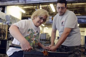 Jamie Schroder of Peters takes a glass blowing class, called Hot Glass Blowout, from Zach Layhew of Blawnox, who is an instructor at the Pittsburgh Glass Center in Friendship.