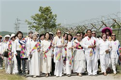 U.S. activist Gloria Steinem, sixth from right, Nobel Peace Prize laureates Mairead Maguire, from Northern Ireland, second from right, and Leymah Gbowee, from Liberia, third from right, and other activists march to the Imjingak Pavilion on Sunday with South Korean activists along the military wire fences near the border village of Panmunjom, in Paju, north of Seoul, South Korea.