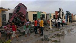 Residents stand outside their homes Monday as damaged cars are seen after a tornado hit the town of Ciudad Acuna, state of Coahuila. At least 13 people died on Monday morning after the tornado hit.